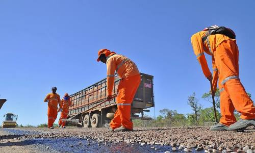 Trabalhando em metade da pista visando não parar totalmente o trânsito, os trabalhadores ajustam as falhas na brita colocada pelo caminhão
