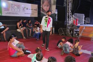 Thiago Ramos interage com as crianças cantando e dançando.