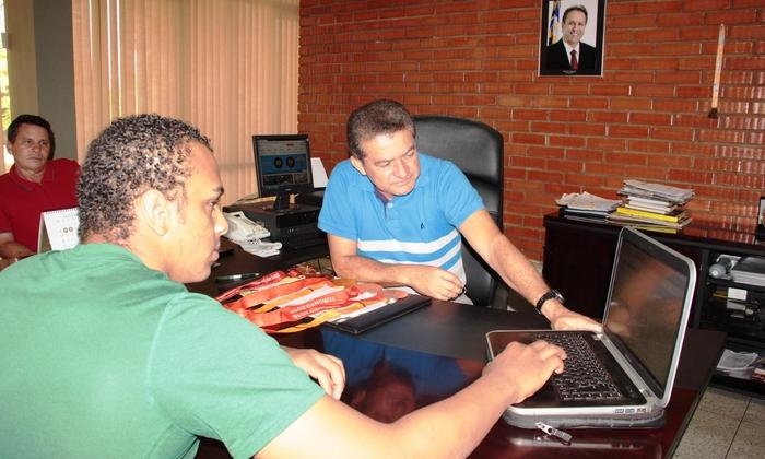 Ítalo Gomes Pereira (E) mostra pelo computador a Salim Milhomem algumas conquistas em sua trajetória pelo mundo