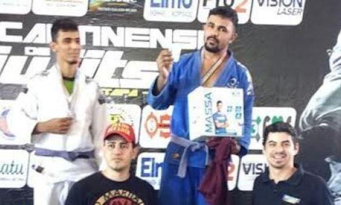 Tiago, de quimono azul, no pódio, após conquista_700x420.jpg