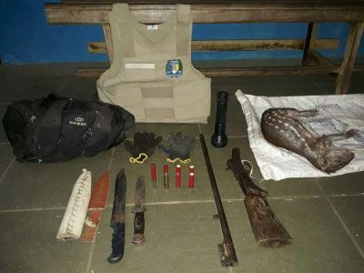 Arma de fogo, paca, e demais objetos apreendidos em posse do suspeito.