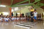 Agente de Trânsito do Detran ensinando aluno da educação infantil  a usar a faixa de pedestre