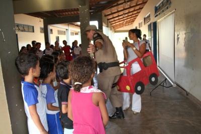 De forma ludica a equipe demonstra ás crianças  como acontece o atropelamento do pedestre por um condutor fazendo uso do celular ao volante
