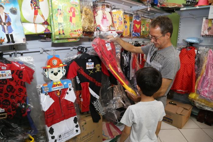 Marcelo Noleto e o filho Vínicius observando os preços  de presentes.JPG