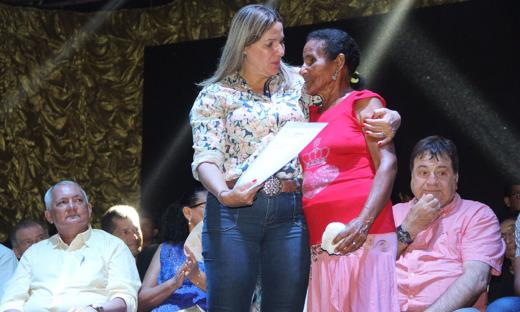 A deputada federal Dulce Miranda entrega título a moradora