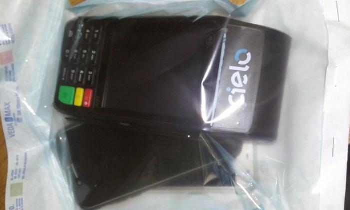 Com os estelionatários, a PM apreendeu uma máquina de cartão de crédito, dois aparelhos celulares e dois cartões de crédito