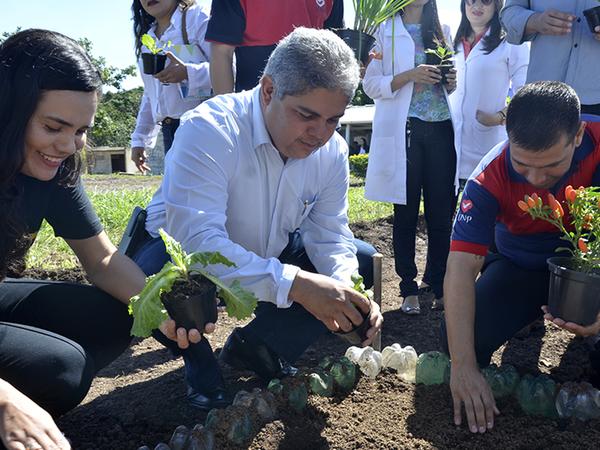 Secretário da Seciju, coronel Glauber, planta muda de alface no canteiro inaugural da horta