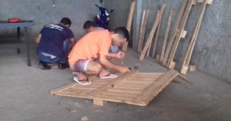 Adolescente utilizando palete para produção de móveis
