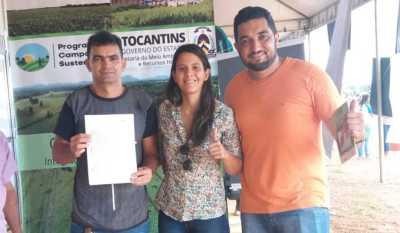 O agropecuarista Carley Adriano (esq.) recebe o documeto de adesão ao CAR dos técnicos da Semarh na feira