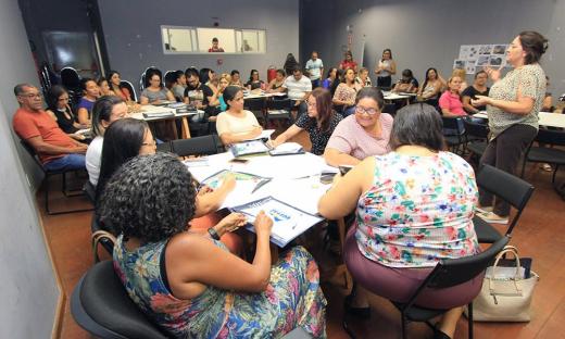 Professores observam as orientações da professora Nelma Maria Martins de como trabalhar na prática a Educação Fiscal dentro do currículo escolar
