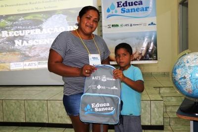A dona de casa Nubia Guedes e o seu filho Leandro recebem kit educativo do Educa Sanear