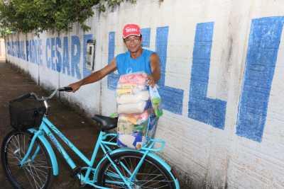 Em sua bicicleta, Adão Barbosa dos Santos leva para casa os kits dos seus dois filhos matriculados na Escola Estadual Padre Césare Lelli