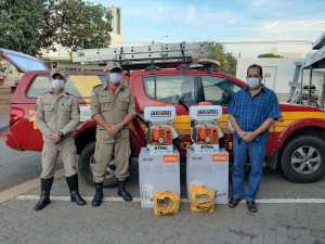 Empresário Ivan Naves (D), com bombeiros militares na entrega dos pulverizadores costais