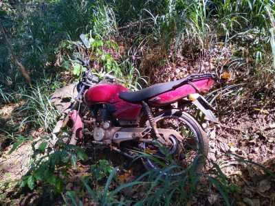 Moto escondida no matagal.