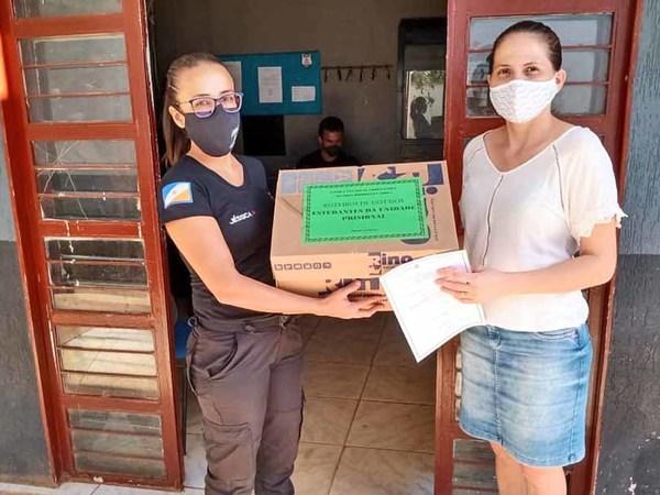 A diretora da Escola Professora Alcides Rodrigues Aires entrega o kit do aluno, higienizado, à agente de execução penal da CPP de Porto Nacional