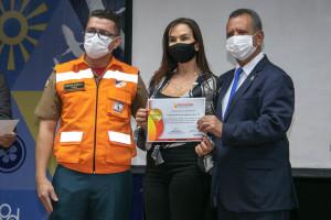 O coronel Carlos Eduardo Farias, subcomandante do CBMTO (E), e o governador em exercício, Antônio Andrade, entregam certificado a um dos parceiros das ações